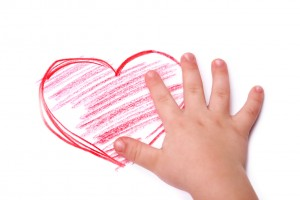 The children's hand is located in heart drawing